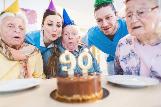 Senior men and women celebrating birthday in retirement home