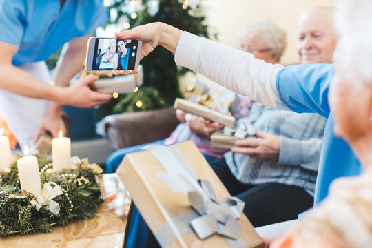 Seniors and nurses taking Christmas pictures in nursing home
