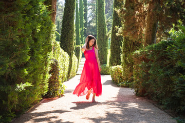 Pretty girl in red dress walking in green park