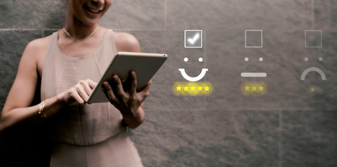 Wall Mural - woman pressing face emoticon on virtual touch screen at smartphone .Customer service evaluation concept.