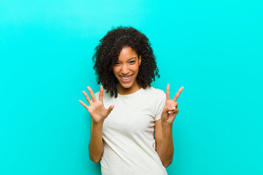 young black woman smiling and looking friendly, showing number seven or seventh with hand forward, counting down against blue wall