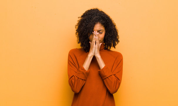 young pretty black woman feeling worried, hopeful and religious, praying faithfully with palms pressed, begging forgiveness against orange wall
