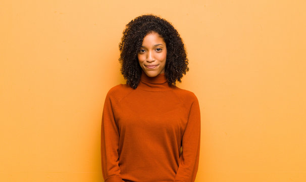 young pretty black woman smiling positively and confidently, looking satisfied, friendly and happy against orange wall