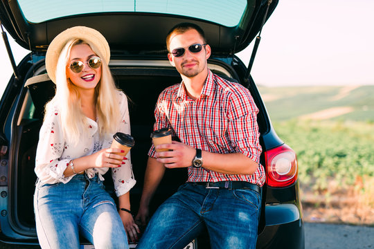 Beautiful young couple sitting with coffee in car trunk