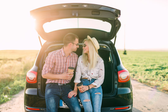 Young happy couple sitting in car trunk outdoor. Road trip