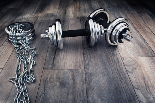 metal dumbbells for fitness and chain on a wooden floor