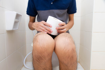 Young man sitting in the toilet with holding tissue