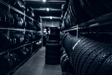 Dark storage full or big variety of new tyres at busy warehouse. Wall mural