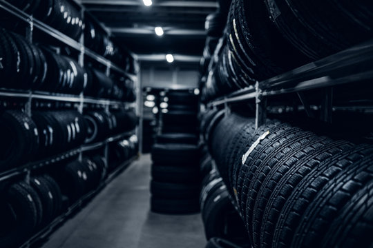 Dark storage full or big variety of new tyres at busy warehouse.
