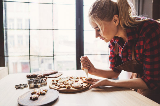 Christmas bakery. Woman decorating Christmas gingerbread cookies with sugar icing. Festive food, cooking process, family culinary, Christmas and New Year traditions concept