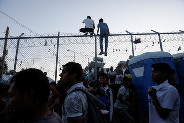 Two migrants climb a fence as others are gathered following a fire in Moria camp on the island of Lesbos