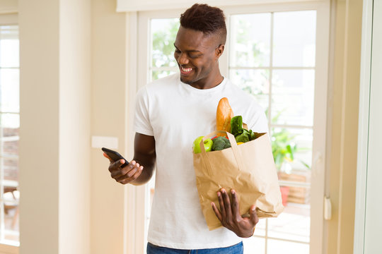African man holding a paper bag full of groceries and using smarpthone buying online using app smiling
