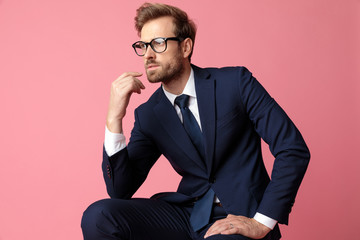 businessman sitting with resting hands and looking away pensive Wall mural