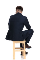back view of young businessman sitting on wooden chair