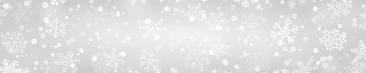 Christmas horizontal banner of snowflakes of different shapes, sizes and transparency in gray colors