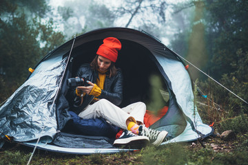 Wall Mural - photographer tourist traveler take photo on camera in camp tent in foggy rain forest, hiker woman shooting mist nature trip, green tourism, rest vacation camping holiday