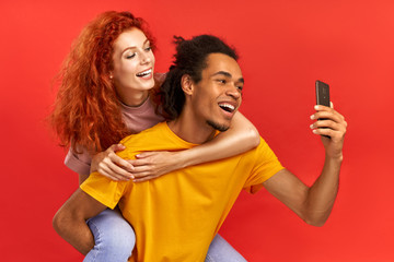 Funny young mixed couple take selfie on smartphone, enjoy piggyback ride, have happy expressions, lovely woman hugs boyfriend from back, isolated over red background. People, fun, leisure time concept