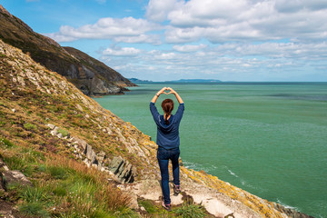 Woman hiker at the edge of a cliff making a heart symbol with her hands and looking towards the sea. Nature love concept.  Irish coast landscape on a sunny summer day.