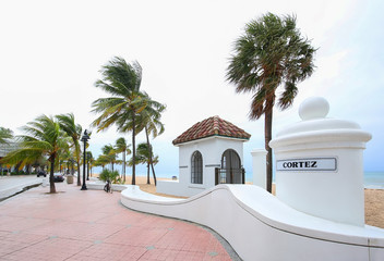 Palm trees sway as the wind blows at the wave wall Cortez Street beach entrance on A1A in Fort Lauderdale Beach, Florida, USA.