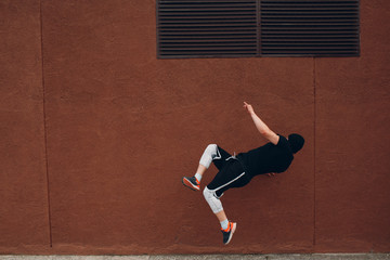 Parkour young man making acrobatic trick and flip jumping high