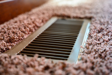 Focus on floor vent in room with carpet