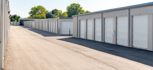 Mini garages of a storage unit facility with trees