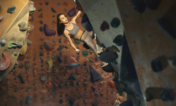 Young female climber Climbing Inside climbing Gym. slim pretty Woman Exercising At Indoor Climbing Gym Wall.