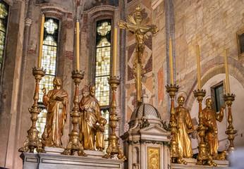 Detail of golden sculptures of saints decorating altar inside catholic church