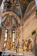 Golden sculptures of saints decorating altar in catholic church in Italy
