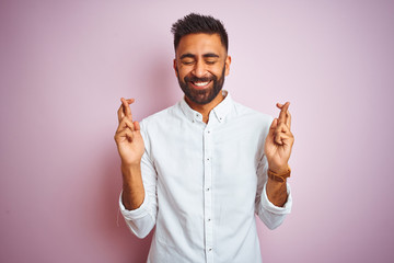 Young indian businessman wearing elegant shirt standing over isolated pink background gesturing finger crossed smiling with hope and eyes closed. Luck and superstitious concept.