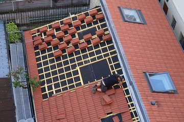Couvreur posant des tuiles sur le toit d'une maison