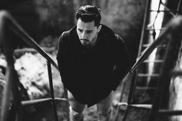 B&W portrait of a handsome young man on stairs in abandoned industrial hall