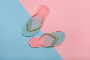 Stylish beach flip-flops on pink and blue pastel background, top view. Summer minimalism concept with copy space.