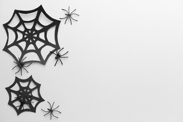 Paper web and spiders as decor for Halloween party on white background