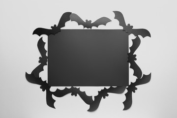 Blank card and paper bats for Halloween party on white background