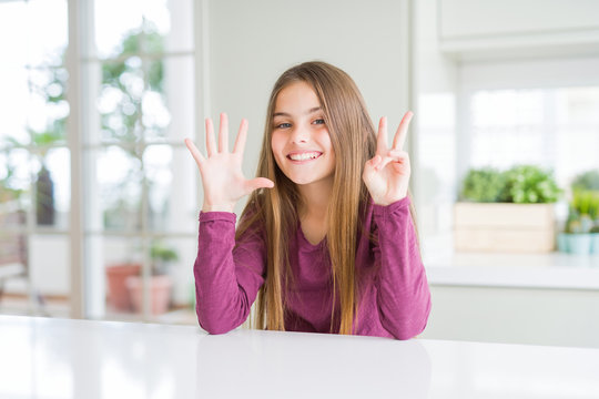 Beautiful young girl kid on white table showing and pointing up with fingers number seven while smiling confident and happy.