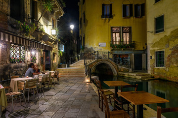 Narrow canal with bridge and tables of restaurant in Venice, Italy. Architecture and landmark of Venice. Night cozy cityscape of Venice.
