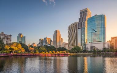 City Park with Lake under Skyscrapers at Sunrise. Benjakiti Park in Bangkok, Thailand