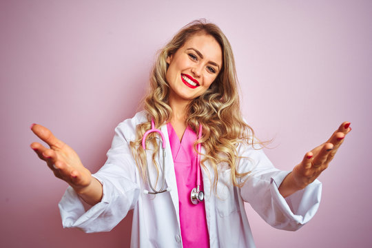 Young beautiful doctor woman using stethoscope over pink isolated background looking at the camera smiling with open arms for hug. Cheerful expression embracing happiness.