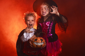 happy children girl and boy in costumes of witch and vampire in dark red background in halloween.