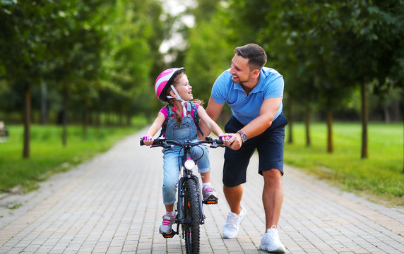 happy family father teaches child daughter to ride a bike in the Park