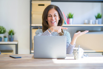 Middle age senior woman sitting at the table at home working using computer laptop amazed and smiling to the camera while presenting with hand and pointing with finger.