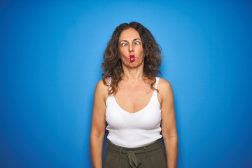 Wall Mural - Middle age senior woman with curly hair standing over blue isolated background making fish face with lips, crazy and comical gesture. Funny expression.
