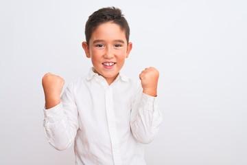 Beautiful kid boy wearing elegant shirt standing over isolated white background celebrating...