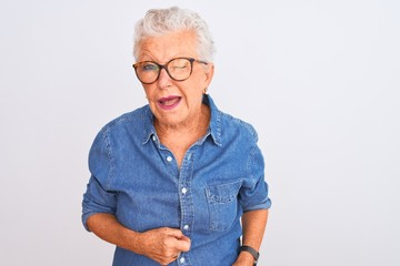 Senior grey-haired woman wearing denim shirt and glasses over isolated white background winking looking at the camera with sexy expression, cheerful and happy face.