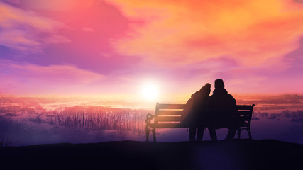 Couple on a bench looks at a winter sunset.