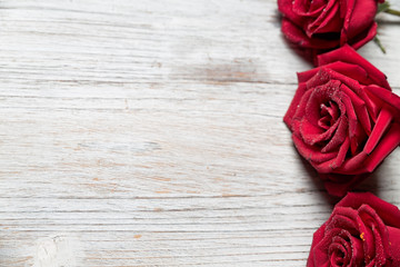 Three Red roses on light wooden background with copy space, top view  - Image