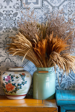 Antique beautiful flower paint ceramic vase and bouquet of dry flowers in green metal pot with vintage ceramic wall tiles background interior decoration on wooden table