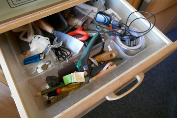 Looking into a untidy drawer.  Messy drawer with tools, household items and various other objects