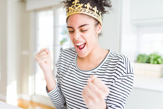 Young african american girl wearing golden queen crown on head very happy and excited doing winner gesture with arms raised, smiling and screaming for success. Celebration concept.